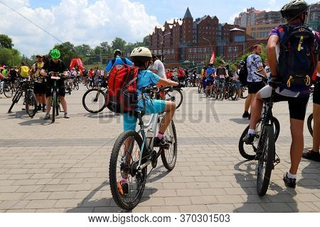 A Boy With A Big Red Backpack Rides A Bicycle Down The Street At A Sports Festival Bicycle Day. A Gr