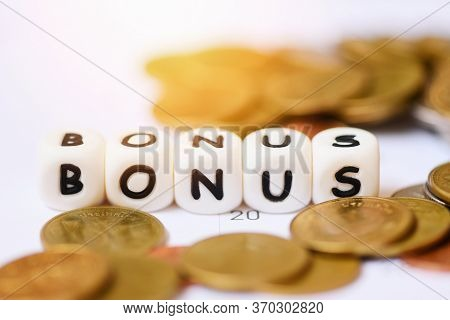 Yearly Bonus Concept / Words Of Bonus And Stack Coins On Calendar Background For Encouragement Moral