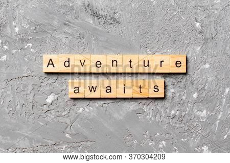 Adventure Awaits Word Written On Wood Block. Adventure Awaits Text On Cement Table For Your Desing,