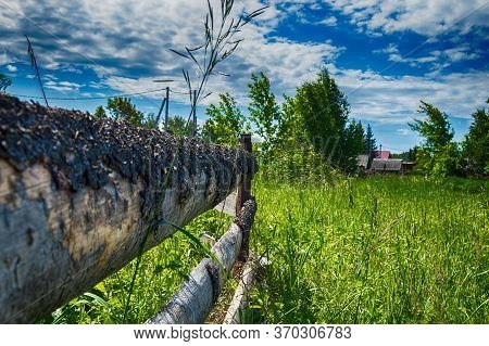 Village Fence Close Up Against The Background Of Houses And Woods On A Sunny Day In Hdr Quality