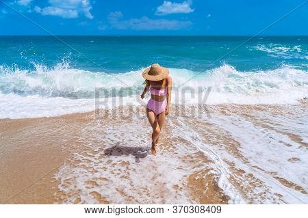 A Girl Walks On The Ocean Foam On A Sandy Beach. Beautiful Girl On The Background Of The Ocean In Th