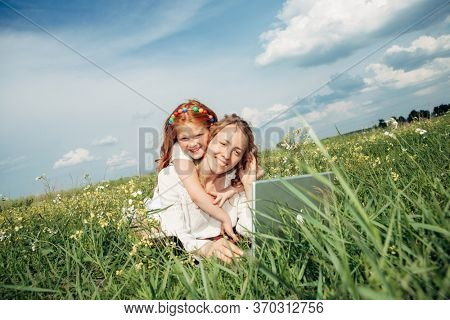 woman with daughter with laptop on grass