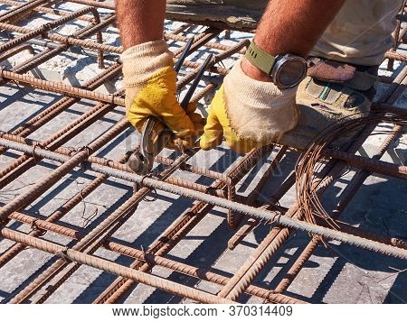 Hands Of Worker Tying Reinforcement Rebars With Haywire
