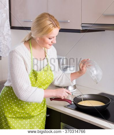 Smiling Young Housewife Making Omlet At Home Kitchen