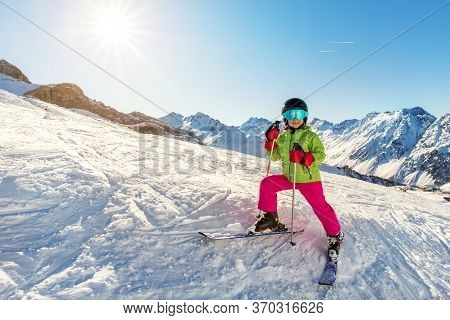 Cute Adorable Little Young Skier Child Girl In Bright Ski Sport Suit Having Fun Riding Mountain Ski