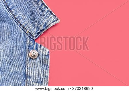 Close-up Blue Denim Jacket On Pink Background Top View Flat Lay Copy Space. Denim, Fashionable Jacke