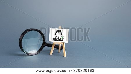 Magnifying Glass And An Easel With A New Hired Employee. Recruiting And Hr Management. Hiring New Wo