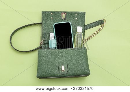 Handbag, Phone, Nail Polish  And Disinfection; Gel On Green Background. Monochrome. Minimal.