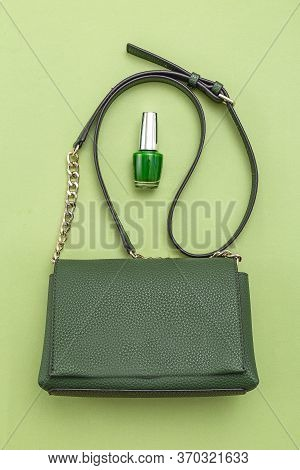 Handbag Green Color And Nail Polish On Green Background.  Monochrome. Vertical Format.