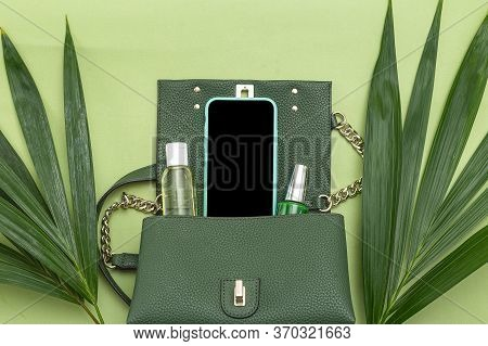 Handbag, Phone, Nail Polish And Natural Leaves On Green Background. Monochrome. Flat Lay