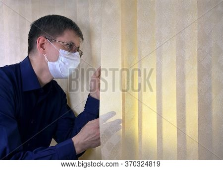Man In A Medical Facial Mask Looks Out Through The Jalousie. Quarantine, Do Not Go Outside Because O