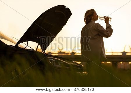 Silhouette Of Woman Drinking Water From A Refillable Bottle, Tired Of Waiting For Assistance Near He