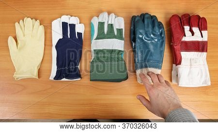 Gloves Are Laid Out On The Table And Have Different Degrees Of Protection. A Person Decides Which On