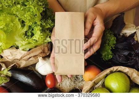 Organic Vegetables In Eco Bag In Market. Woman Seller With Craft Paper Bag And Products In Organic F
