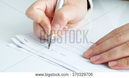Closeup Image Of Person Signing Banking Cheque