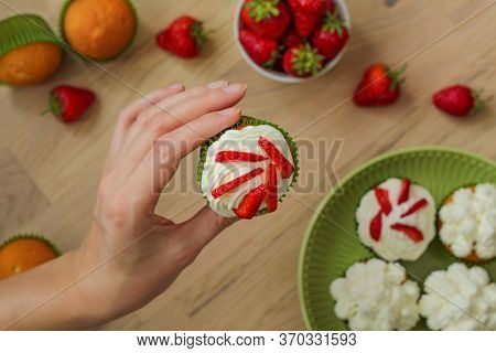 Homemade Muffin In The Hand Against The Background Of Strawberries And Muffins With Caps Of Cream.