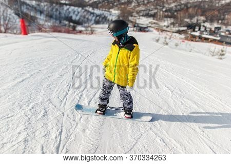 Snowboarder In Black Helmet, Yellow Jacket Glides Down On A Blue Snowboard On The Ski Slope