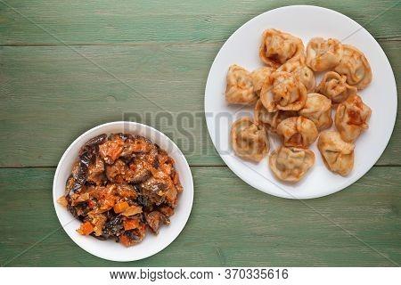 Dumplings On A White Plate On Green Wooden Background. Dumplings In Tomato Sauce With Salad. Dumplin
