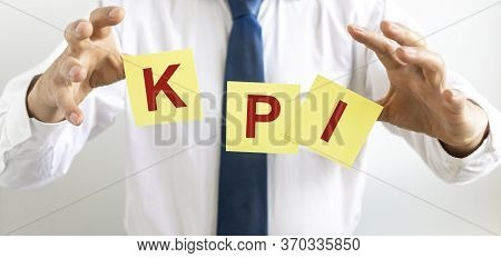 Kpi Key Performance Indicator Written On Yellow Notes Papers Flying Between Male Hands Of Businessma