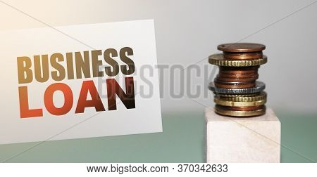 Business Loan On A Card And Stack Of Coins. Business And Finance Concept. Interest And Fees From Loa
