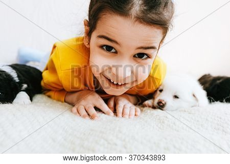 Closeup Image Of An Adorable Child Has Joyful Expression Playing At Home With Little Dogs. Pretty Li