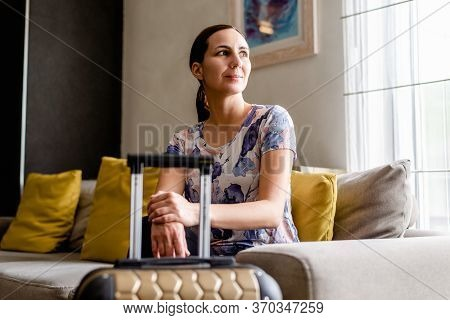 Traveler Woman In Hotel Room In Vacation. Woman Traveler Relaxing In Vacation. Traveler With Luggage