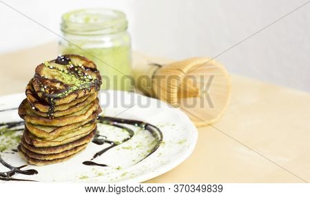 Matcha And Banana Pancakes With Black Chocolate, Next To Green Matcha Powder And Bamboo Matcha Whisk