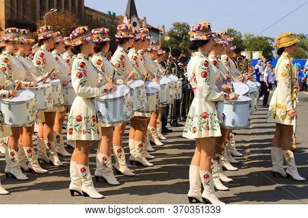 Drummer Girls In Beautiful White Costumes And Fashionable Hats With Bright Flowers Stand At The City