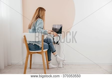 Focused Young Freelance Woman Sitting On The Table At Home With Laptop And Headphones, Working Remot