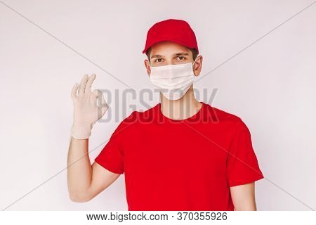 Portrait Young Happy Delivery Service Courier In Medical Face Mask And Protective Glove Show Ok Sign