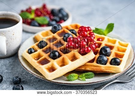 Belgian Waffles With Berries And Cup Of Coffee On Plate, Closeup View. Tasty Sweet Breakfast Food