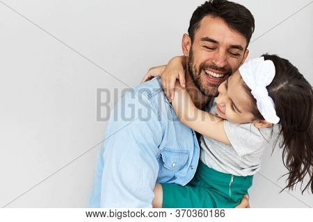 Studio Image Of The Happy Father Embraces His Cute Daughter. Loving Daddy And His Little Girl Smilin