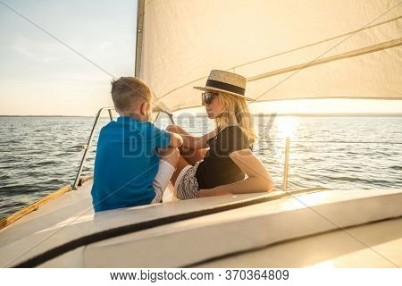 Happy traveler mother and son enjoying sunset from deck of sailing boat moving in sea at evening time. Bonding Travel, Summer, Holidays, Journey, Trip, Lifestyle, Yachting concept.