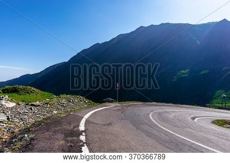 Mountain Road On A Sunny Morning. Empty Highway Uphill Through Valley.  Great European Journey In Su