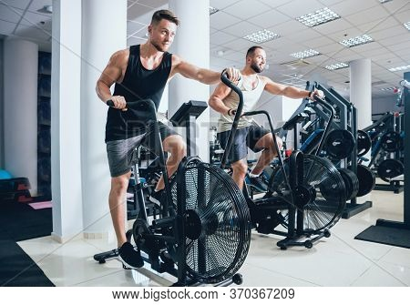 Young Men With Muscular Body Using Air Bike For Cardio Workout