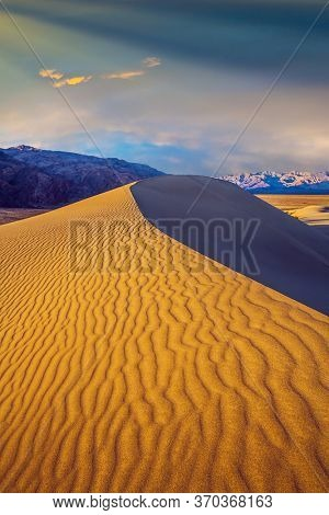 Magical desert morning. Mesquite Flat Sand Dunes - dunes in Death Valley. USA. The sand lies in light waves. The dunes are located along Road 190. The concept of active and photo tourism