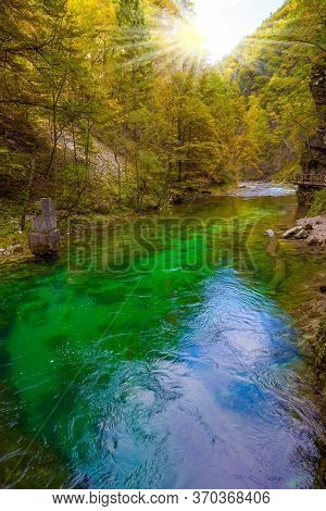 Sun illuminates quiet backwater with emerald water. Slovenia. Vintgar gorge. The concept of active and photo tourism