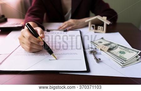 Real Estate Agent's Hand Pointing Signature Client In Contract Form On Table With Money, Purchase Ag