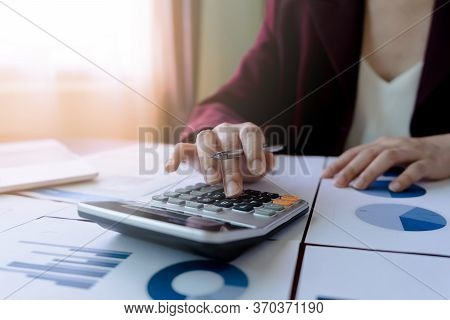 Business Woman Or Accountant Working With Pen And Press Calculator To Calculate Finance Report, Data