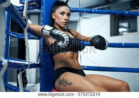 Side View Of Professional Female Kickboxer With Strong Face Wearing Black Sports Underwear And Boxin