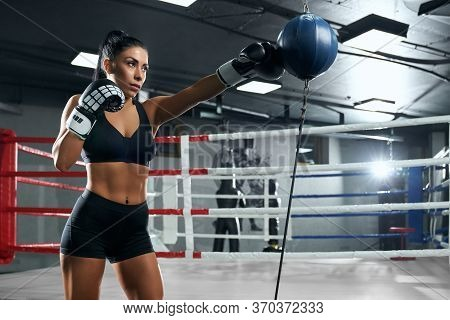 Side View Of Muscular Woman With Strong Face Wearing Boxing Gloves And Black Sportswear Hitting Boxi