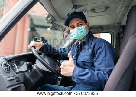 Masked truck driver giving thumbs up during coronavirus pandemic