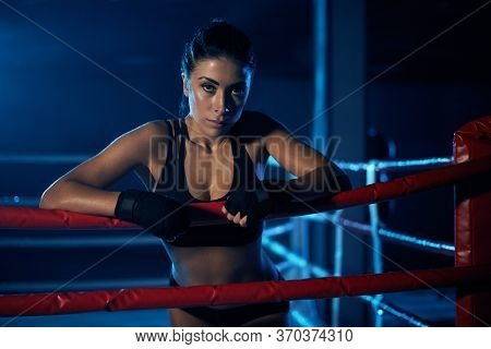 Serious Young Professional Female Kickboxer Wearing Black Sportswear And Bandages On Hands, Posing I