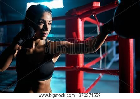 Close Up Of Fit Brunette Woman With Strong Face Wearing Boxing Gloves And Black Top Hitting Boxing B