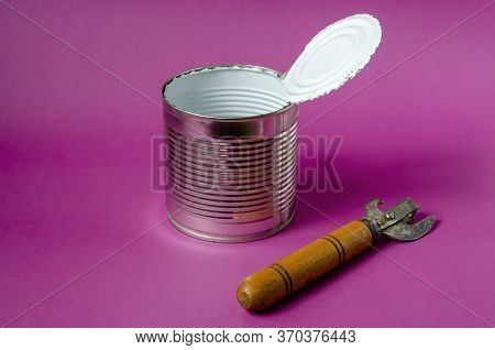 An Old Can Opener Lies Next To An Empty Tin Can On A Purple Background. Open Tin Can With White Food