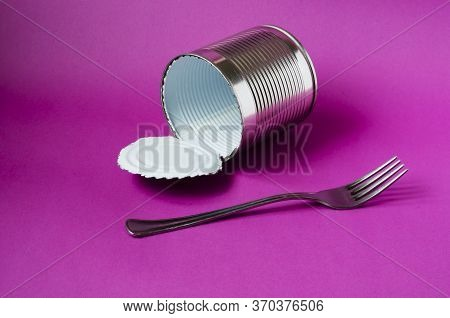 Empty Tin Can And Fork On A Purple Background. Tin Can With White Enamel Inside And A Metal Fork. Ca