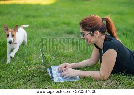 A Woman With Glasses Lies On The Green Grass In The Park With Her Own Dog. A Girl Blogger Maintains