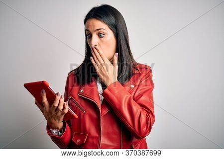 Young brunette woman with blue eyes using touchpad tablet over isolated background cover mouth with hand shocked with shame for mistake, expression of fear, scared in silence, secret concept