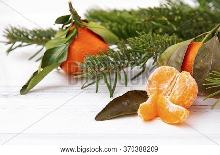 Slices Of Fresh Peeled Tangerine, Whole Tangerines, Spruce Branches On A White Background