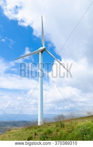 Windmills Used To Generate Energy, In The Foreground With Sky And Sunny Blue Day..